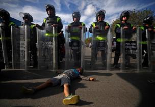 طفل يرقد على الأرض أمام قوات مكافحة الشغب المكسيكية
