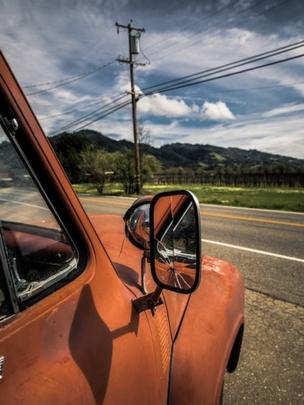 Broken rearview mirror on an old orange truck.