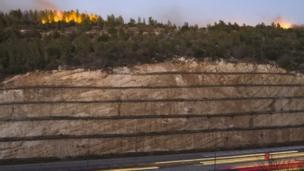 A forest fire burns on the ridge above the main Route 1 linking Tel Aviv to Jerusalem