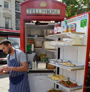 A phone box containing a fridge and various salad items for sale