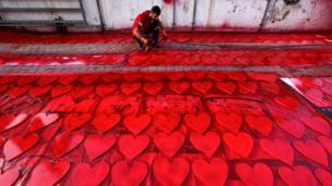 伊拉克庫爾德人在埃爾比勒街頭為情人節慶祝做凖備,他用油漆噴槍為心形圖案上紅色。