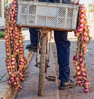 Box containing onions on the back of a bicycle