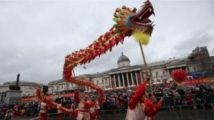 """Members of the Chinese community perform a """"dragon dance"""" in a front of a crowd backed by the National Gallery"""
