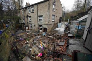 Flood water flows past terraced houses in Stalybridge