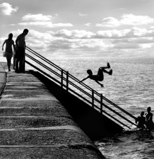 A boy somersaults from the promenade into the sea