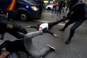 الدفاع المدني الإسباني يسحب المتظاهرين خارج مركز الاقتراع في برشلونة يوم اجراء استفتاء حول استقلال إقليم كتالونيا