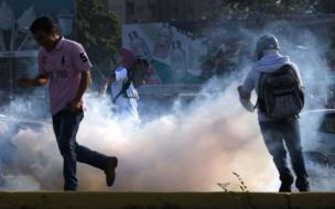 Manifestantes huyen de gases lacrimógenos