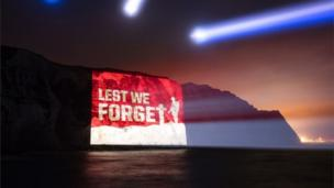 Image saying 'Lest we forget' projected onto the side of the White Cliffs at Dover