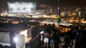 Habitantes de las favelas durante la inauguración ven el estadio Maracaná de lejos
