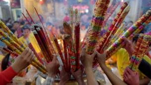 Cambodian-Chinese place various sizes of incense sticks into an urn at a temple to mark the start of the Lunar New Year in Kandal on February 16, 2018