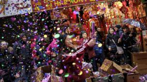 A woman pops confetti during a cultural festival to mark the first day of the Lunar New Year in Chinatown neighborhood in Manhattan, February 16, 2018 in New York City.