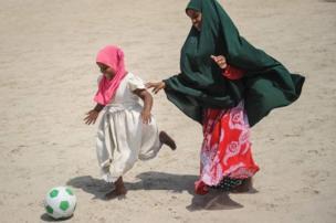 فتاتان تلعبان كرة القدم