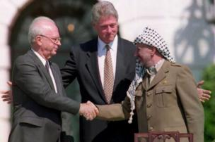 US President Bill Clinton (centre) stands between PLO leader Yasser Arafat (right) Israeli Prime Minister Yitzhak Rabin, as the two shake hands.