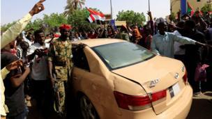 محتجون يحيطون بسيارة أحد الضباط، ويرددون هتافات غاضبة بعد بيان الجيش.