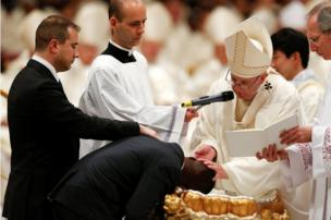 Pope Francis baptizes a man as he leads the Easter vigil mass in Saint Peter's Basilica at the Vatican