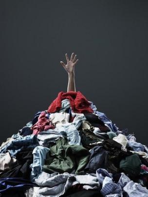 Una mano saliendo de una montaña de ropa para lavar