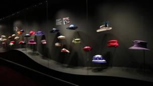 """A woman looks at Britain""""s Queen Elizabeth""""s hats at an exhibition at Buckingham Palace in London"""