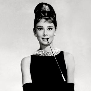 Audrey Hepburn in black dress, pearl necklace, beehive hair and long black gloves