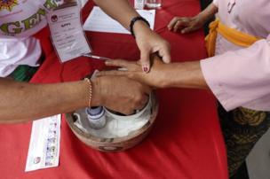 Bali'de bir kadın oy verdikten sonra parmağını mürekkep boyasına sokuyor.