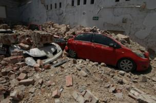 Cars dey buried for under di rubble.