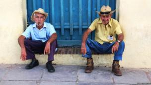 Two men smoking on cigars and sitting on a doorstop in Trinidad