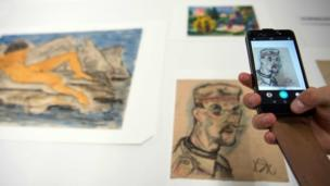 A journalist takes a picture with a mobile phone of the art pieces coming from the estate of German collector Cornelius Gurlitt during a press preview of the first masterpieces of the estate of Gurlitt at the Museum of Fine Arts Bern (07 July 2017)