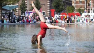 فتاة تؤدي حركات استعراضية بالوقوف على يديها، بينما كانت تسعى للتغلب على ارتفاع درجات الحرارة في حمام سباحة بميدان المتاحف بالعاصمة الهولندية أمستردام.