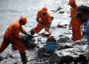Members of the Pollution Response Team remove black oil washed ashore as a thick oily tide from the sea lapped at the coast