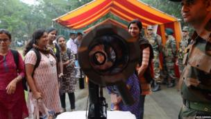 2. An Indian student looks into a rocket launcher during the Army Day celebration at a college in Chennai (
