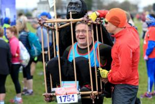 A runner helps a man in fancy dress to adjust his gorilla costume