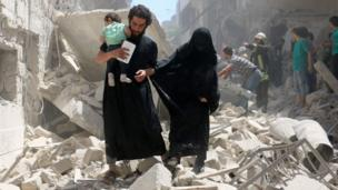 A family walks amid the rubble of destroyed buildings following a reported air strike on the rebel-held neighbourhood of al-Kalasa in the northern Syrian city of Aleppo, on April 28, 2016.