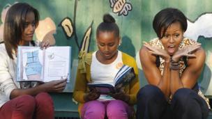 Malia, Sasha da Michelle Obama na karantawa yara littattafai a Johannesburg, a shekarar 2011