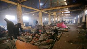 Mülteciler soğuktan ve yağmurdan kaçmak için terkedilmiş bir binaya sığındılar.