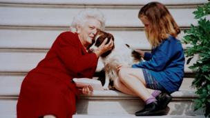 Barbara Bush pets her dog Millie while waiting with her grandaughter Barbara for President George H.W. Bush to arrive on White House steps in this undated photo in Washington, DC.