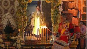 King Maha Vajiralongkorn lighting a candle during the ceremony