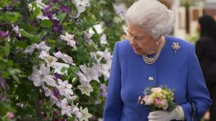 The Queen looks at a floral display