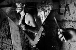 2008 في مدينة نابولي. امرأة تقف امام مرآة وتمسك بحقنة في يدها.