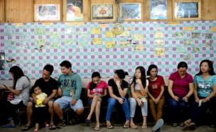 A line of voters of different ages and genders, seated while they wait to vote, in a polling station in Davao