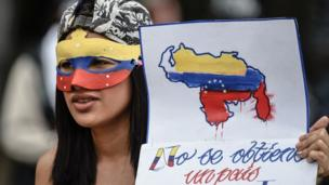 "A young opposition activist holds a sign reading ""we can't get a different country"", during a protest against the government in Caracas, on June 29, 2017"