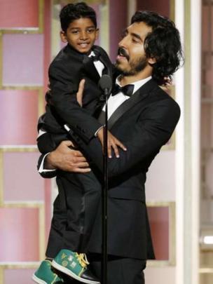 Dev Patel (phải) giúp bạn diễn nhỏ tuổi trong phim Lion Sunny Pawar lên vừa tầm microphone.