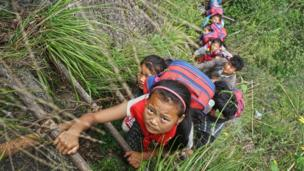Children of Atuler Village climb the vine ladder on a cliff on their way home in Zhaojue county in southwest China's Sichuan province on May 14, 2016 in Zhaojue, China