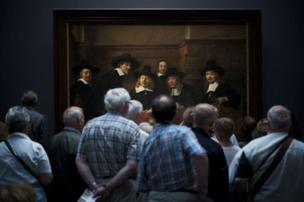 """Second place was Julius Y's photograph, taken in front of Rembrandt's painting Syndics of the Drapers' Guild. By photographing the crowd in front of the painting, he said this, """"gave the illusion that the people in the painting are also curiously watching the visitors""""."""
