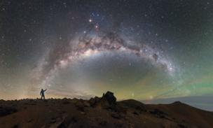 شخص يقف وتظهر السماء الحالكة تضيئها النجوم