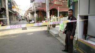 A policeman behind police tape at the site of one of two bomb blasts which occurred on 11 August 2016 in Hua Hin, Thailand. Still image taken from video shot on 12 August 2016.