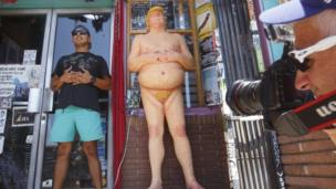 A man poses next to a Donald Trump statue in Los Angeles
