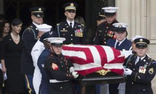 The McCain family and an honour guard in military uniforms pictured with his flag-draped casket