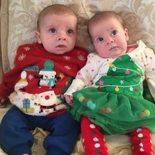 Two babies wearing Christmas jumpers