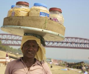 A man balances tubs of snacks on his head.
