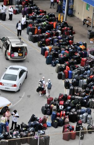 Hundreds of suitcases are are placed on the ground ready to be loaded onto a ship