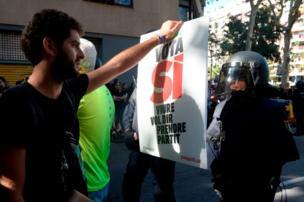 Barcelona'da bir protestocu, üstünde 'Evet oyu ver' yazılı bir pankartı İspanyol polisin yüzüne tutuyor.